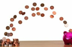 pennies and coins moving into a piggy bank - how to save for a vacation