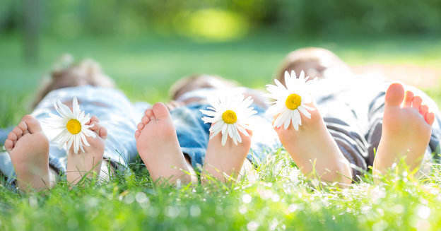 family lying down in the grass with daisies