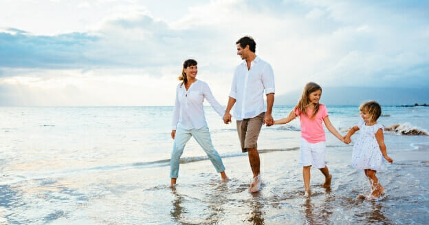 young family walking on beach - how to save for a vacation