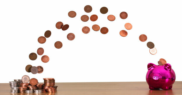 how to stop spending money - pile of coins with coin arch going into pink piggy bank
