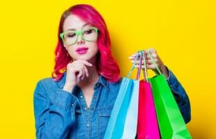 girl with 3 shopping bags against yellow background