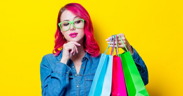 how to stop spending money - girl with 3 shopping bags against yellow background