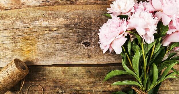 being frugal - pink flowers and string on a wood background