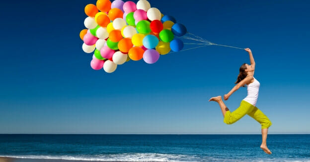 being frugal - girl jumping with colourful balloons