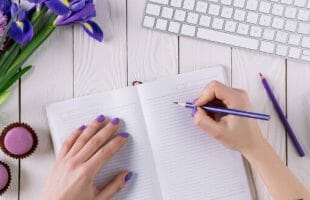 woman writing in a notebook with pencil with flowers - frugal living bloggers