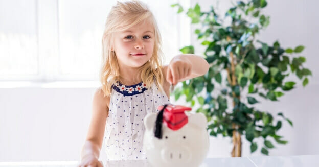 small girl putting money in piggy bank